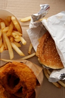 Photo of generic fast food, including French fries, a hamburger and onion rings.
